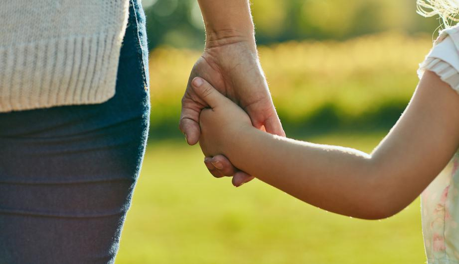 Little girl holding mother's hand in the park.