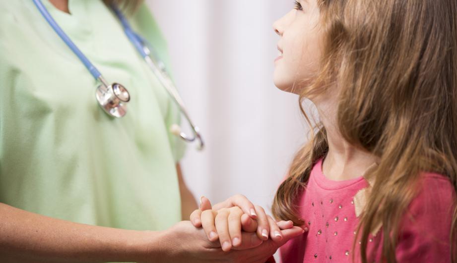 School nurse consoles, holds hand child patient.