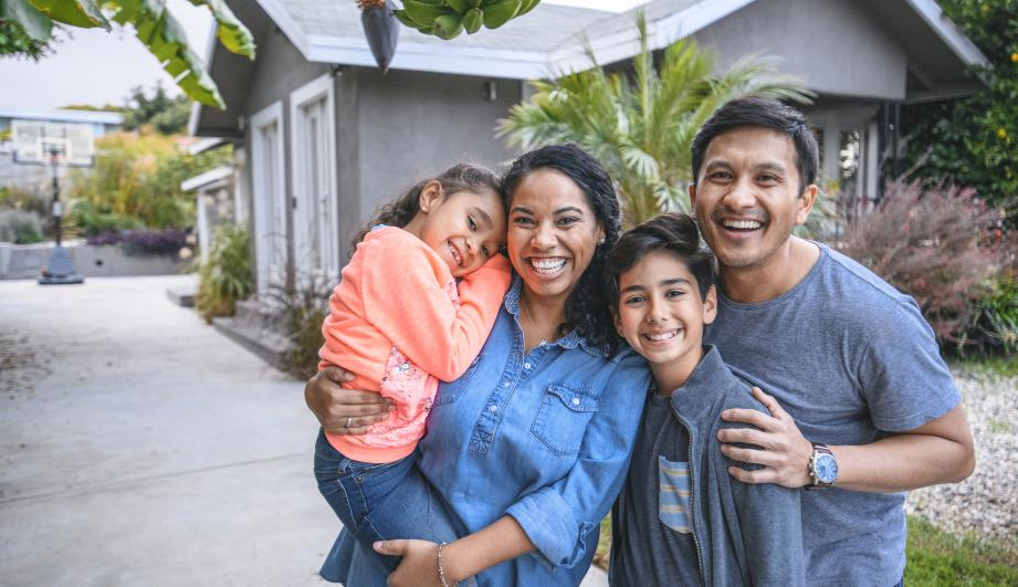 Portrait of happy family against house. Multi-ethnic parents and children are smiling on driveway.