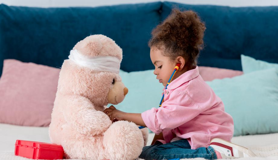Little child in pink jacket playing the doctor with teddy bear