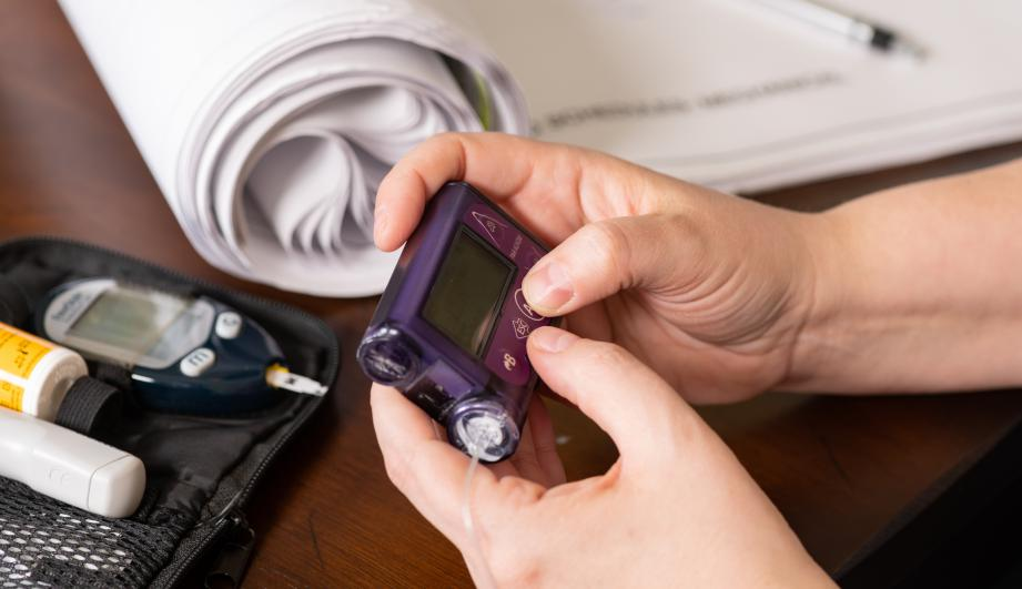 Woman working while using insulin pump and glucose meter to control type 1 diabetes