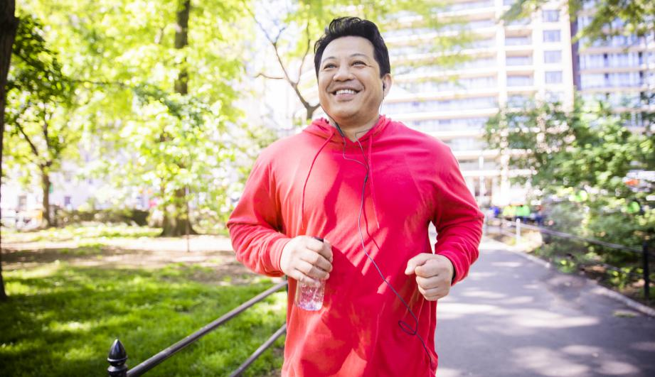 Man in red jacket running in a park.