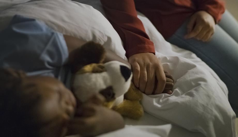 Woman holding son's hand sleeping on a bed. Sleeping boy is with stuffed toy relaxing by mother.