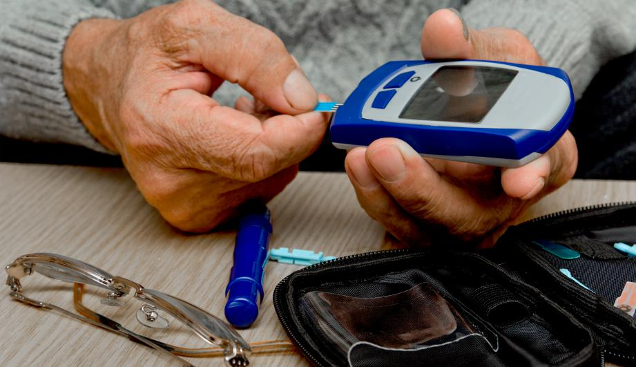 Senior man with glucometer checking blood sugar level at home.