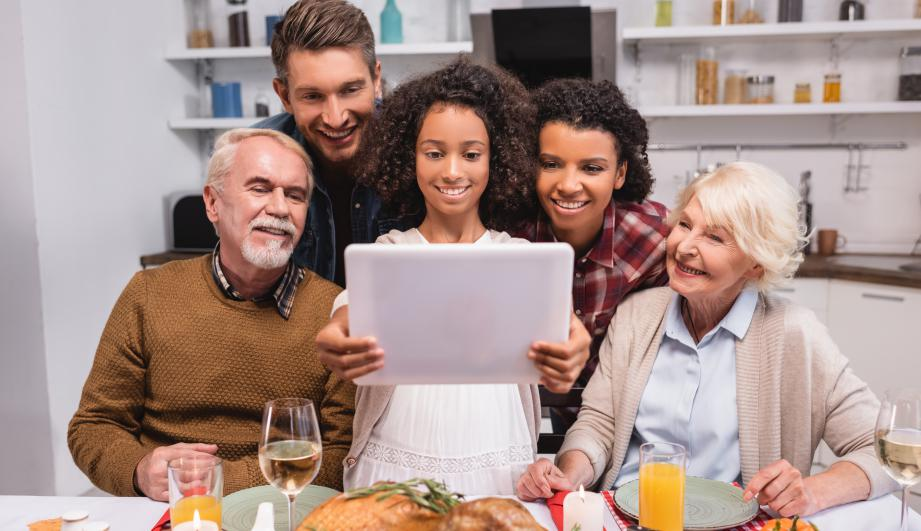 girl holding digital tablet near parents during thanksgiving celebration