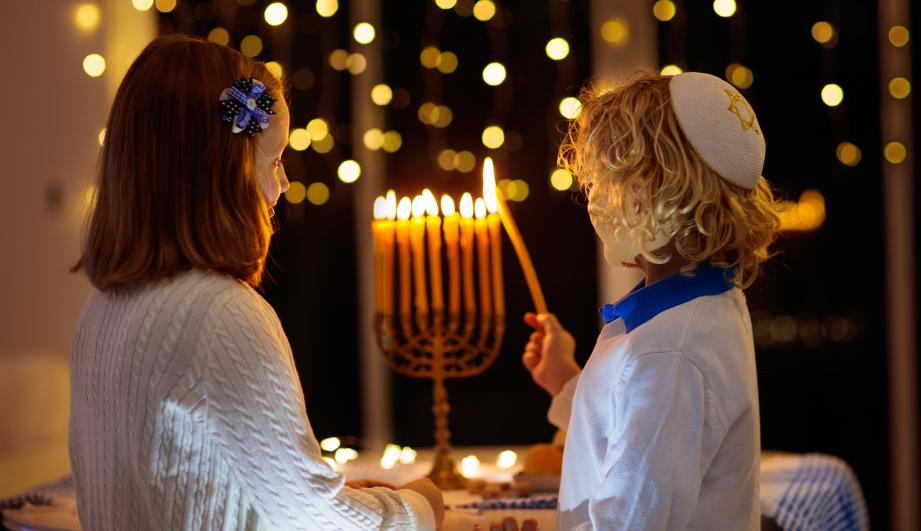 Kids celebrating Hanukkah. Jewish festival of lights. Children lighting candles on traditional menorah. Boy in kippah. Israel holiday.
