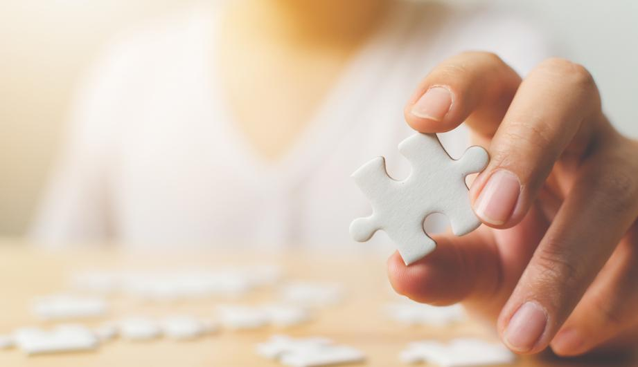 Hand of male trying to connect pieces of white jigsaw puzzle on wooden table. Healthcare for Alzheimer disease, dementia, memory loss, autism awareness and mental health concept