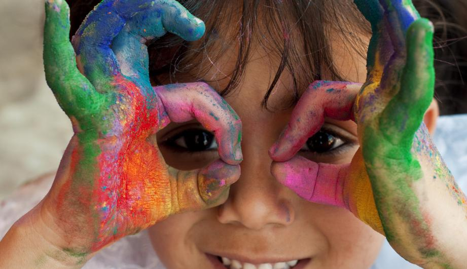 young girl with paint on her hands smiling