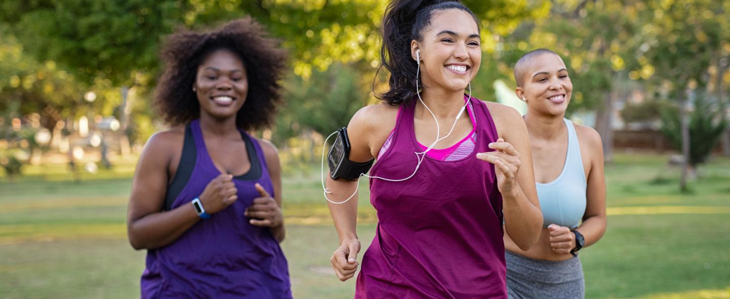 Smiling young women running at the park on a sunny day.