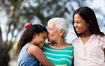 Affectionate senior woman embracing and kissing granddaughters