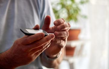 A man monitoring his blood sugar with glucose meter
