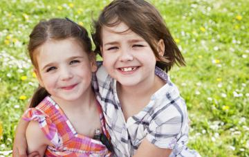 young girl with diabetes, insulin pump visible at neckline of dress, and her sister, hugging
