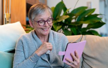 Senior woman holding tissue engaged in telehealth consulting on smart phone