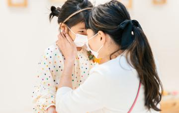 Mother putting protective mask on her daughter`s face