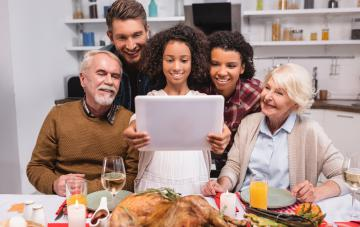 girl holding digital tablet near parents during thanksgiving celebration