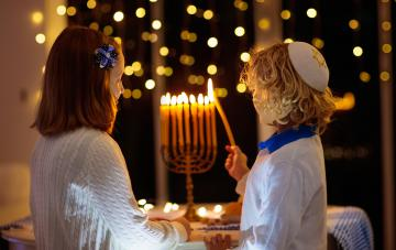 Kids celebrating Hanukkah. Jewish festival of lights. Children lighting candles on traditional menorah. Boy in kippah. Israel holiday.
