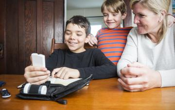 Boy at home with his family supporting him as he reads his blood glucose (sugar) levels on a glucose meter or glaucometer.
