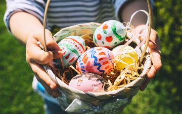 Colorful Easter eggs in basket. Children gathering painted decoration eggs in spring park. Kids hunt for egg outdoors.