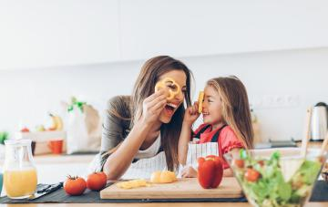 Mother and daughter having fun cooking with the vegetables