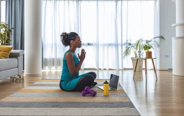 Yoga teacher with hands together in anjali mudra praying pose on chest in living room. Middle aged woman sitting in padmasana with props around her. Working from home, female yogi practice concepts