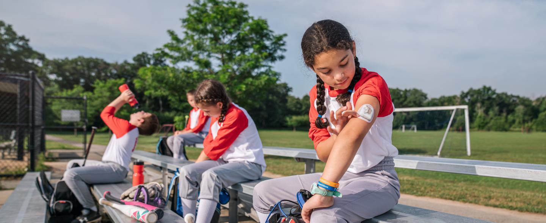 Mackenzie, a pediatrics patient at Joslin, checks her insulin pump before taking the softball field.