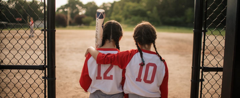Mackenzie, a pediatrics patient at Joslin, walks on the softball field with her best friend.