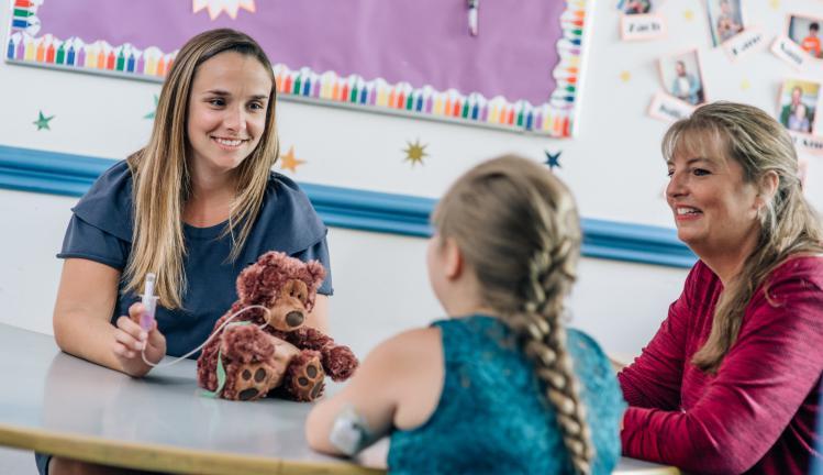 Child Life Specialist Jessica Allen with pediatric patient in Joslin's playroom.