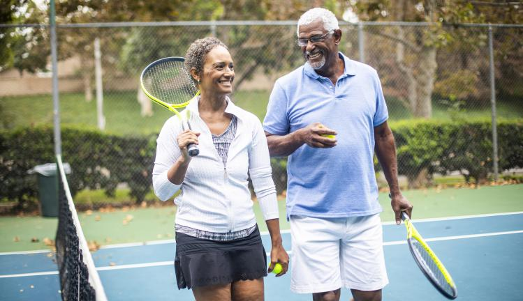 Senior black couple playing doubles tennis.