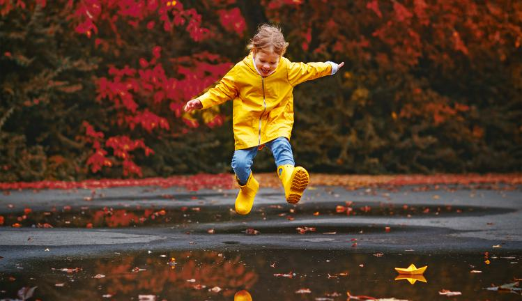 Happy girl in rain coat and rubber boots jumping in puddle on autumn walk