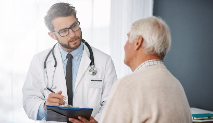Doctor going through medical records with his male patient.