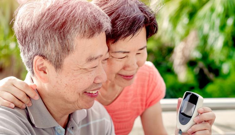 Older asian couple checking blood sugar level.