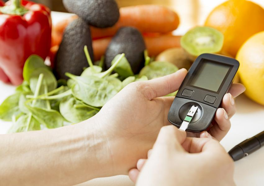 Diabetes monitor, diet and healthy food eating nutritional concept with clean fruits and vegetables with diabetic measuring tool