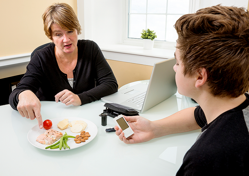 Diabetes Educator consulting with a teenage diabetes patient on glycemic index