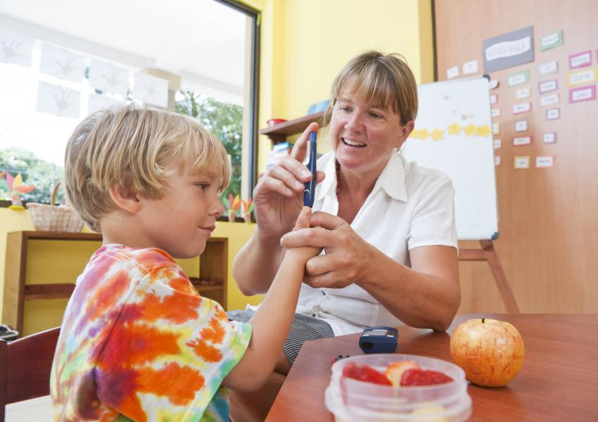 School Nurse with type one boy testing blood sugar.