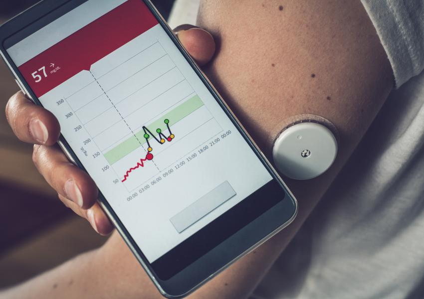 Woman checking glucose level with a remote sensor and mobile phone, sensor checkup glucose levels without blood. Diabetes treatment