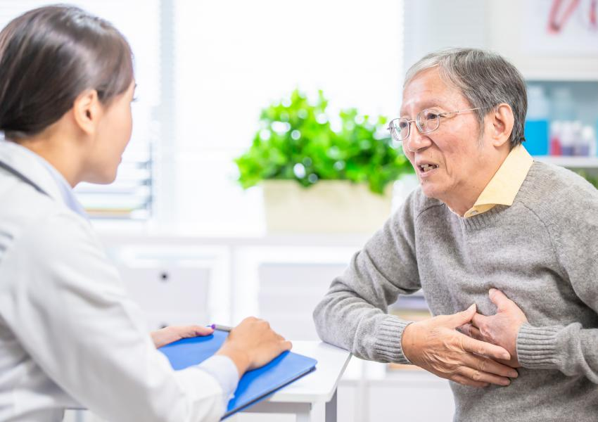 Older asian man discussing symptoms with female doctor