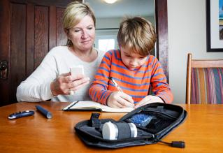 Juvenile diabetes patient with his mother recording his levels
